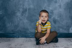 A young emotional boy sits on a wooden floor against the background of a blue wall in the studio. Human emotions. A young emotional boy sits on a wooden floor royalty free stock image