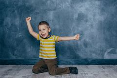 A young emotional boy sits on a wooden floor against the background of a blue wall in the studio. Human emotions stock images