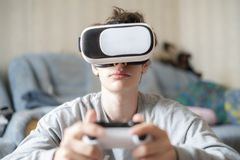 Young emotional boy using virtual reality vr headset at home and play games f royalty free stock photos