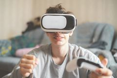 Young emotional boy using virtual reality vr headset at home and play games f royalty free stock image