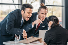 Young emotional businesspeople in formalwear arguing at meeting in office. Business team meeting stock photography