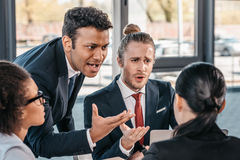 Young emotional businesspeople in formalwear arguing at meeting in office. Business team meeting stock photos