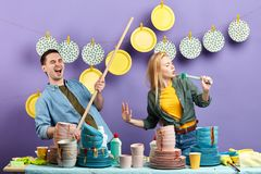 Young emotional couple using brush and broom to dance and sing royalty free stock images