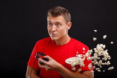 The emotional guy is holding a joystick from the game console and scattered popcorn. Black background. The young emotional European brunette guy is holding a Stock Photos