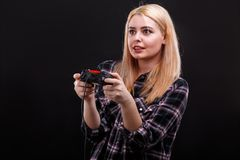 Emotional girl plays with a game joystick with a very scared look. On a black background. Young emotional girl, blonde, European appearance, fascinatingly plays stock photo