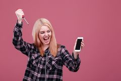 Young emotional girl holds a smartphone and aggressively swings a screwdriver. On a pink background. Young emotional girl blonde, European appearance, holds a Stock Images