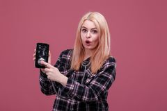 Emotional girl holds a broken mobile phone and attached a stratoscope to him. On a pink background. Young emotional girl blonde, European neshnosti, holds a stock image