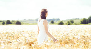 Young, emotional and happy woman in a meadow of rye. Beautiful g Stock Photo