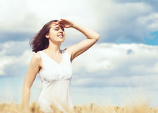Young, emotional and happy woman in a meadow of rye. Beautiful g Stock Image