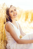 Young, emotional and happy woman in a meadow of rye. Beautiful g Stock Photos