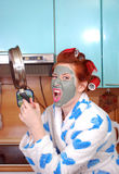 The young emotional housewife with red hair in hair curlers and with a clay mask on a face in rage threatens, having threatened a Stock Image