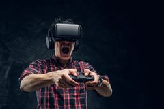 Emotional man using VR headset and playing a video game with joystick in a studio against the background of the dark. Young emotional man using VR headset and stock photography