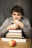 The young emotional student with the books and red apple in class room. At blackboard Stock Images