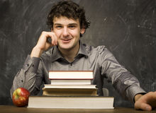 The young emotional student with the books and red apple in class room Royalty Free Stock Photos