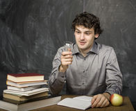 The young emotional student with the books and red apple in class room. At blackboard Stock Photography