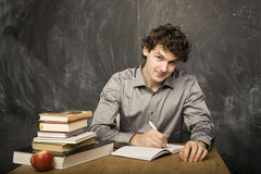 The young emotional student with the books and red apple in class room. At blackboard Royalty Free Stock Photo