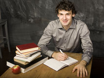 The young emotional student with the books and red apple in class room Royalty Free Stock Photography