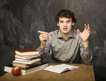 The young emotional student with the books and red apple in class room Royalty Free Stock Images