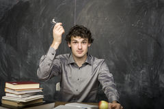 The young emotional student with the books and red apple in class room Stock Photo