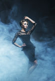 Young and emotional woman in fashion dress on the smoke Stock Photography