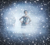 Young and emotional woman in fashion dress on a snowy background Stock Photos