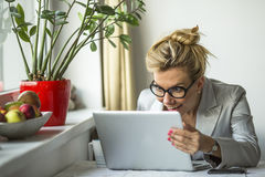 Young emotional  woman looking at the laptop monitor with surprise and joy. Royalty Free Stock Image