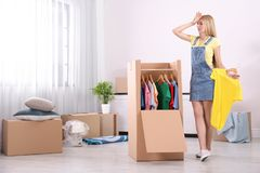 Young emotional woman near wardrobe box. At home stock images