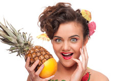 Young emotional woman with pineapple and gr Royalty Free Stock Photos