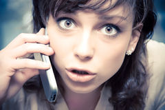 Young emotional woman talking on mobile phone Stock Photos