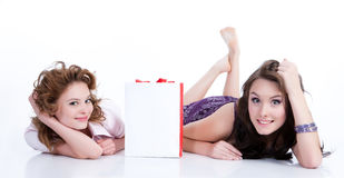 Young Emotional Women With Paper Bag. Two young women with shopping bag smiling royalty free stock images