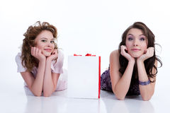 Young Emotional Women With Paper Bag. Two young women with shopping bag lying on a reflecting background and looking towards stock photo