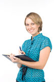 The young employee. The beautiful girl writes in the daily log Royalty Free Stock Image