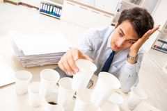 The young employee building pyramid from plastic cups. Young employee building pyramid from plastic cups stock photo