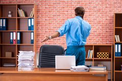 The young employee with excessive work sitting at the office stock image