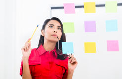 Young employee looking at multiple reminders while planning her. Portrait of young Asian employee looking at multiple reminders while planning her work in the Stock Images