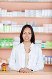Young employee at pharmacies counter Stock Images