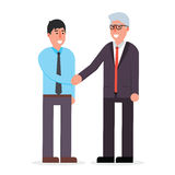 Young employee and senior businessman shaking hands and smiling. Royalty Free Stock Images