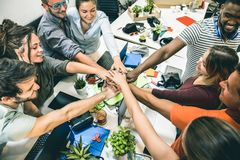 Young employee startup workers group stacking hands at start up office. Employee startup workers stacking hands on entrepreneurship brainstorming project royalty free stock photo