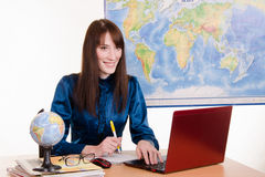 Young employee travel company communicates with customers. Young beautiful employee in the office of the travel agency royalty free stock image