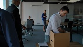Young employee unpack box with docs and equipment. His colleagues walking near in modern office