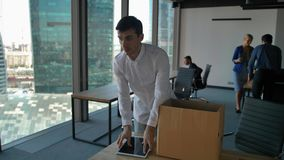 Young employee unpack box with docs and items. His colleagues walk near in modern office stock video