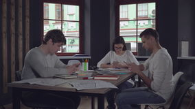 Young employees with client use devices on the meeting. Group of people sitting at the desk using gadgets in the casual contemporary office start up company stock video footage