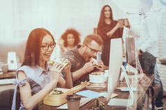 Young Employees. Snack. Sandwiches. Working Desks. royalty free stock photos