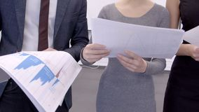 Young employees are studying paper blueprint, standing in modern office. Successful professionals are engaged in business, holding documents in leading company stock footage