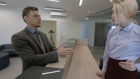 Young employees are talking at reception desk in leading company. Woman and man discuss working business standing in modern office. Beautiful blonde and guy stock video