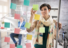 Young employer put her idea on memo stickers Stock Image