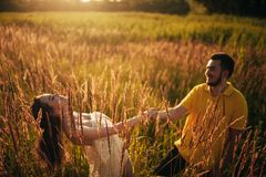 Young enamored couple have fun and smile at meadow. Young enamored couple have fun and smile at meadow against background of grass and spikes. Backlit stock photos