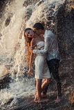 Young enamored couple hugs and kisses under spray of waterfall. Stock Image