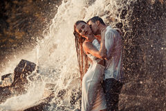 Young enamored couple hugs and kisses under spray of waterfall. Young enamored wet couple hugs and kisses under spray and drops of waterfall. Around them are stock photography