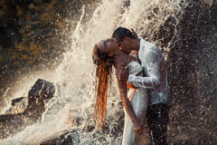 Young enamored couple hugs and kisses under spray of waterfall. Young enamored wet couple hugs and kisses under spray and drops of waterfall. Around them are royalty free stock images